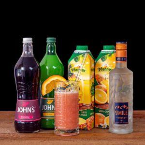Sex On The Beach Cocktail-Paket komplett Bundle mit 9 Mile Vodka, JOHN'S Grenadine & Citrus Sirup, Pfanner Orangensaft und Ananassaft. Auf dem Foto zu sehen ist der fertig gemixte Cocktail sowie alle Zutaten.