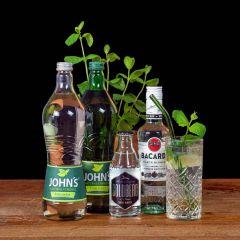 Mojito Cocktail-Paket komplett Bundle mit Bacardi Carta Blanca White Rum, JOHN'S Lime Juice, Rohrzucker Sirup und GOLDBERG Soda Water. Auf dem Foto zu sehen ist der fertig gemixte Cocktail sowie alle Zutaten.