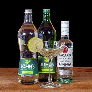 Daiquiri Cocktail-Paket komplett Bundle mit Bacardi Carta Blanca White Rum, JOHN'S Lime Juice & Rohrzucker Sirup. Auf dem Foto zu sehen ist der fertig gemixte Cocktail sowie alle Zutaten.