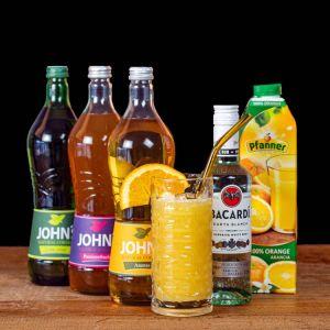 Hurricane Cocktail-Paket komplett Bundle mit Bacardi Carta Blanca White Rum, JOHN'S Lime Juice & Ananas Sirup, Passionsfrucht Sirup und Pfanner Orangensaft. Auf dem Foto zu sehen ist der fertig gemixte Cocktail sowie alle Zutaten.